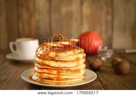 Delicious pancakes with maple syrup and sliced apple on wooden table