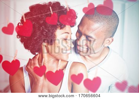 Hearts hanging on a line against close up of couple at home