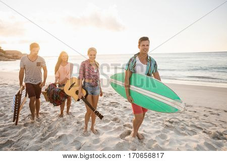 Friends carrying a surfboard and basket at the beach