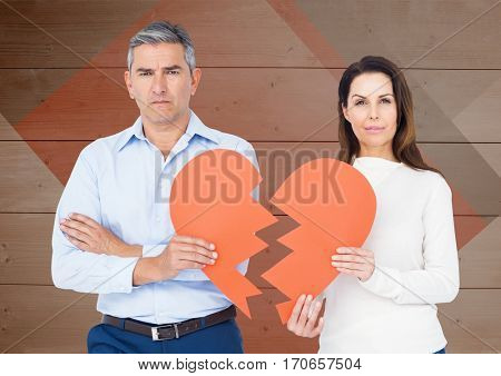 Portrait of sad couple holding broken hearts against wooden background