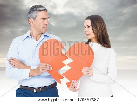 Mature couple holding broken a heart against sky