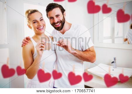 Hearts hanging on a line against portrait of happy couple checking pregnancy test