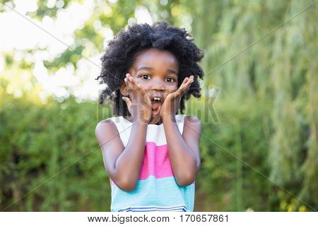 A kid surprised and holding her head in hands on a park
