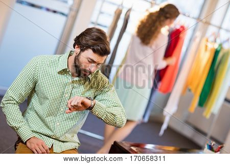 Bored man waiting his wife while woman by clothes rack in a shop