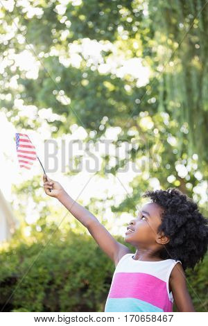 A little girl is holding an american flag in the air in a garden