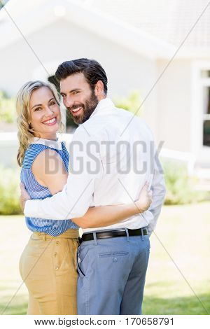 Portrait of happy couple embracing each other outside the house
