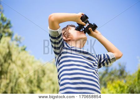 Low angle view of a child looking something with binoculars on a park
