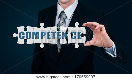 The businessman puts on the virtual puzzles word competence. The business concept