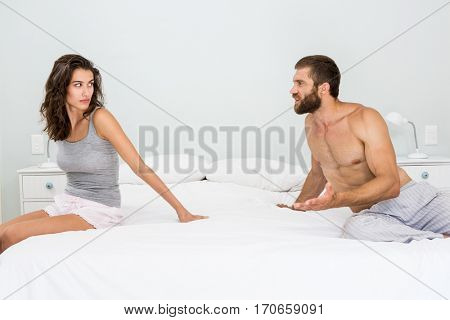 Man arguing with woman on bed at bedroom