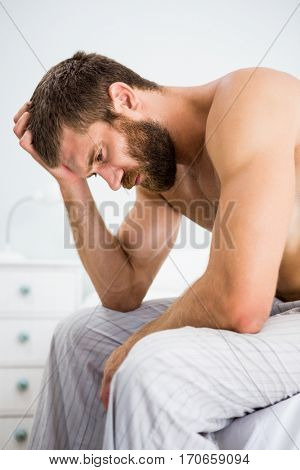 Depressed man with hand on head at home