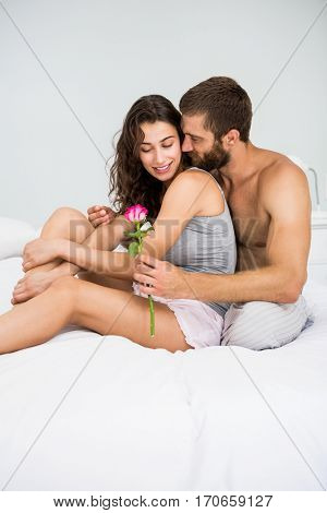 Man offering a rose to woman on bed at bedroom