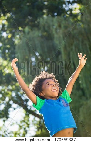 Boy is raising his arms in a park