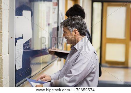 Professor reading notice board in college