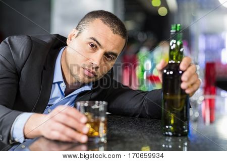 Drunk businessman slumped on bar beside drink