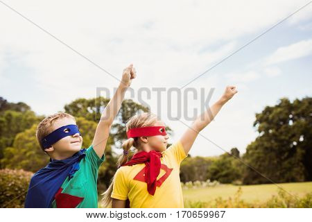 Two cute children pretending to fly in superhero costume in the park