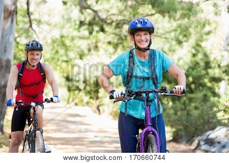 Senior couple standing with their bikes in a fores