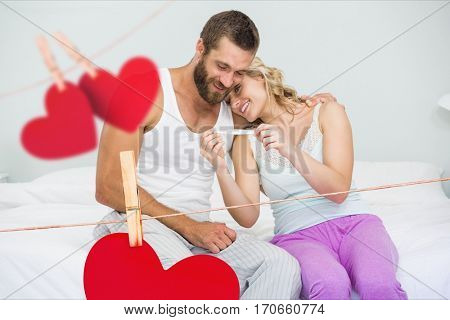 Composite image of red hearts and romantic couple looking at pregnancy test in bedroom at home