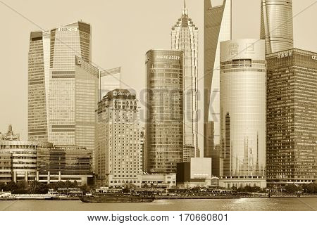 SHANGHAI CHINA - MARCH 25: Pudong district view from The Bund waterfront area on March 25 2016 in Shanghai China. Pudong is a district of Shanghai located east of the Huangpu River. Sepia toned photo
