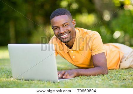 Happy man using his laptop at park