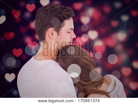 Affectionate couple embracing each other against digitally generated background with hearts