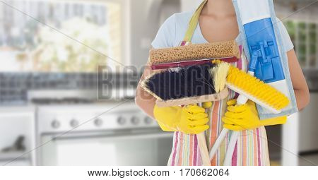 Mid section of woman holding various cleaning equipments in kitchen at home