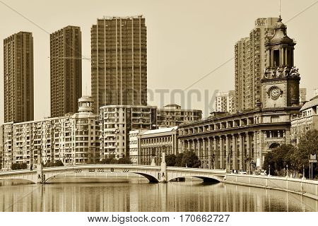SHANGHAI CHINA - MARCH 26: Suzhou Creek on March 26 2016 in Shanghai China. Suzhou Creek (or Soochow Creek) also called Wusong River is a river that passes through the Shanghai city centre. Sepia toned photo