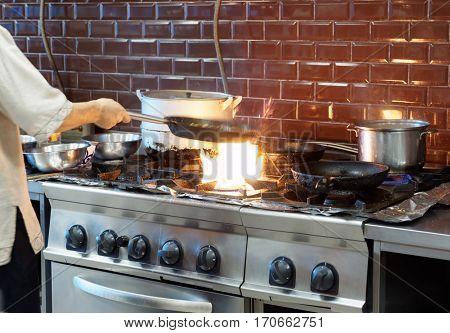 Chef is making flambe dish in restaurant kitchen, motion blur