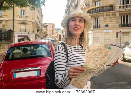 Woman tourist on the street in Paris, look on map under sunlight and blue sky. Famous popular touristic place in the world.