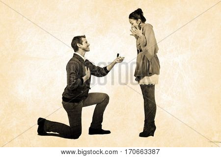 Man offering engagement ring to partner against grey background