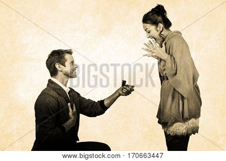 Happy man offering engagement ring to partner against grey background