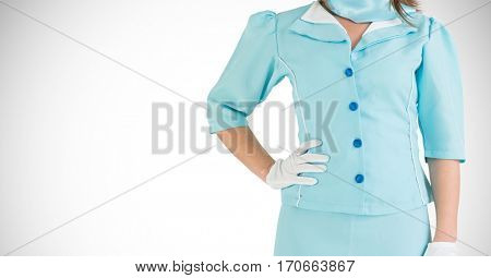 Air hostess in uniform standing with hand on hip against white background