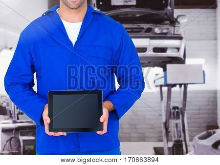 Mid section of mechanic holding a digital tablet at garage