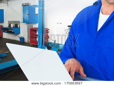 Mid section of mechanic using laptop in repair garage