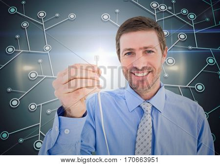 Portrait of businessman holding cable against digitally generated green background