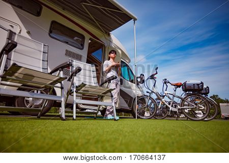 Woman is standing with a mug of coffee near the camper. Caravan car Vacation. Family vacation travel, holiday trip in motorhome