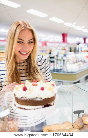 Portrait of woman looking at cake at grocery store