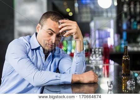 Depressed man having a whiskey in a pub