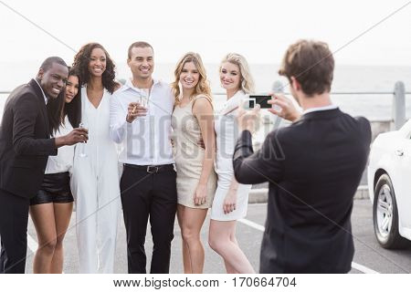 Well dressed people taking pictures next to a limousine on a night out