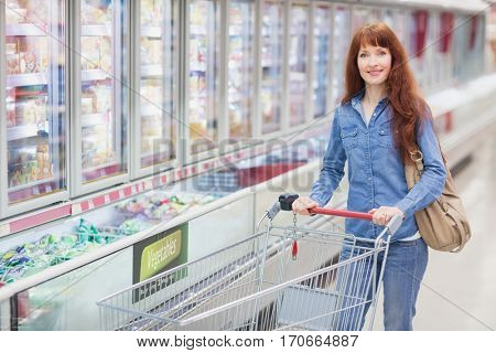 Smiling woman pushing trolley in aisle at supermarket