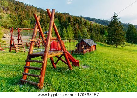 wooden children playground in highland landscape and small cottage