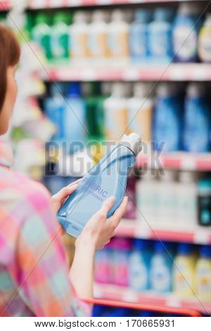 Over shoulder view of woman holding detergent at supermarket