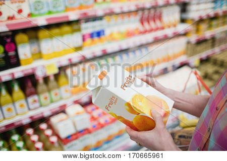 Close up view of hands holding fruits juice at grocery store