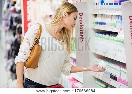 Side view of woman choosing deodorant at supermarket