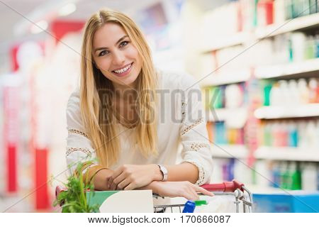 Smiling woman at the supermarket with a full trolley