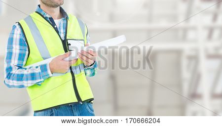 Mid section of construction man standing with blue print