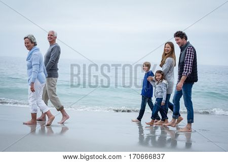 Full length of cheerful multi-generation family walking at sea shore
