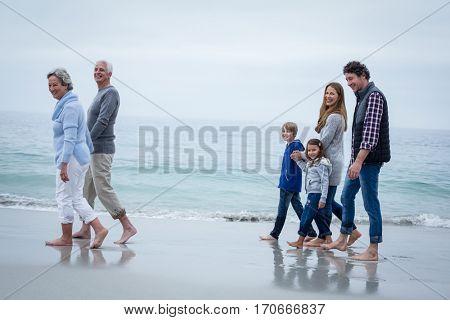Full length of cheerful multi-generation family walking at sea shore