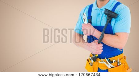 Mid section of handyman holding wrench and plunger with tool belt around his waist against beige background