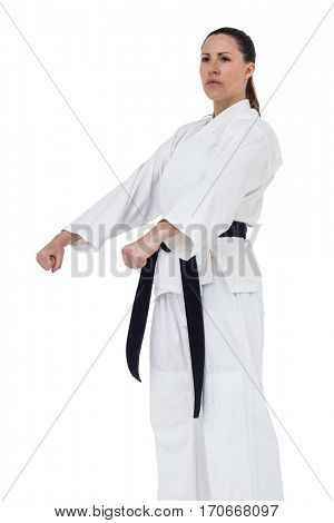 Female fighter performing karate stance on white background