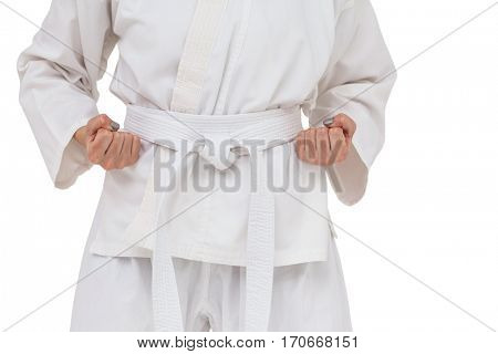 Mid section of fighter performing karate stance on white background